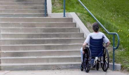 A person in a wheelchair is at the bottom of a flight of stairs.