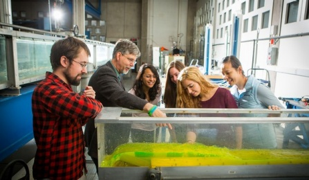 A professor points to something in a tank in front of a group of students.