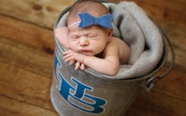 a new born baby in a UB branded bucket