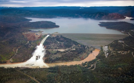 Aerial photo facing east, toward Oroville Dam and Lake Oroville, showing the damaged spillway with its outflow of 100,000 cubic feet per second. Image courtesy of Dale Kolke, California Department of Water Resources. Photo taken February 15, 2017.