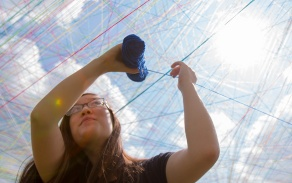 student stringing yarn outside