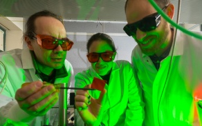 three people in a lab studying a sample