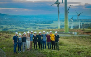 group of people with windmills in the background