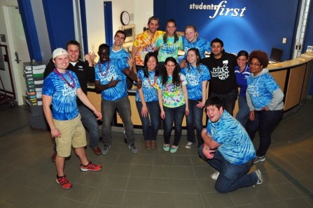 student group gathering around wearing matching tie-dye shirts.