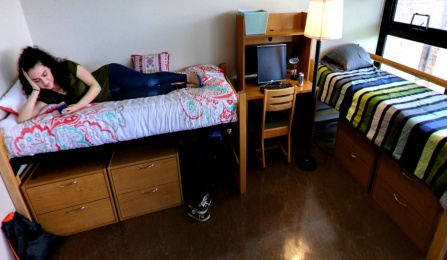 student relaxing on bed in residence hall room.
