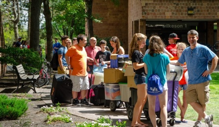 students lined up with belongings waiting to move into the residence hall.
