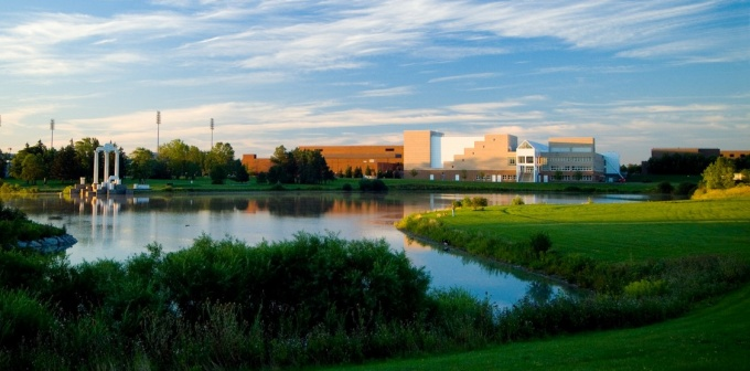 Photo of UB North Campus with blue sky, lake, grass, trees and buildings in background.