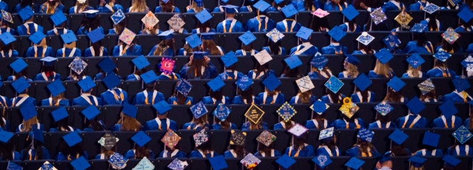 Birdseye view of graduates' caps, many of which are personally decorated.