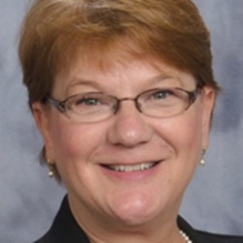 Portrait of Susan Ott smiling into the camera, wearing glasses.