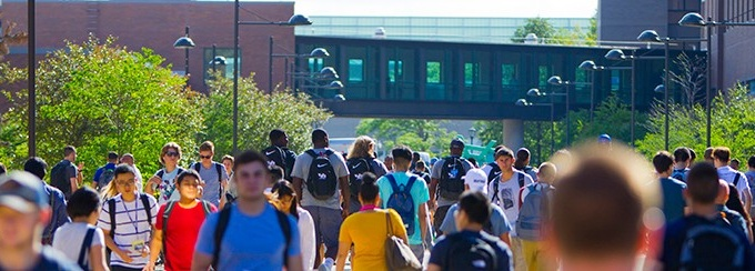 Large amount of students walking outdoors to get to class, on University at Buffalo's North Campus on a sunny day.