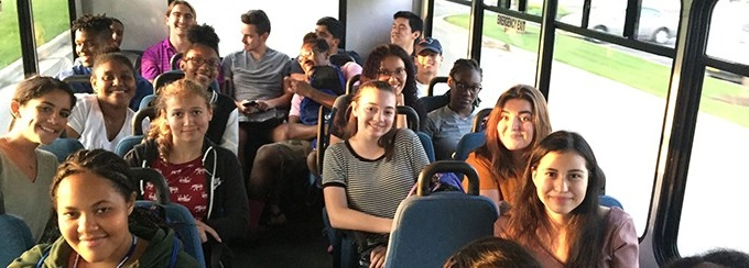Students sitting on a bus and smiling.