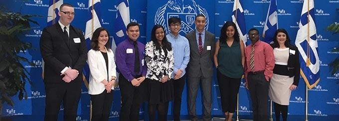 Nine students lined up in front of a blue University at Buffalo backdrop, at an awards ceremony.