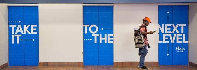 "Three elevator doors closed, with the phrase ""Take it to the next level"" painted across each door; two words per elevator. There is a student standing to the right, looking at his cell phone."