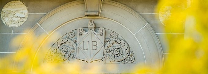 Photo of UB emblem on Foster Hall, with blurred yellow leaves framing the photo, in the foreground.