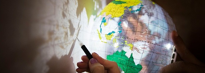 Up-close photo of a clear globe casting a shadow on a wall, and a person tracing the outline of a country with a pencil.