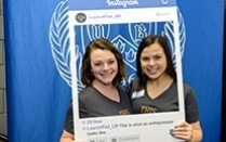Two students at a Blackstone event with a large Instagram frame around them.