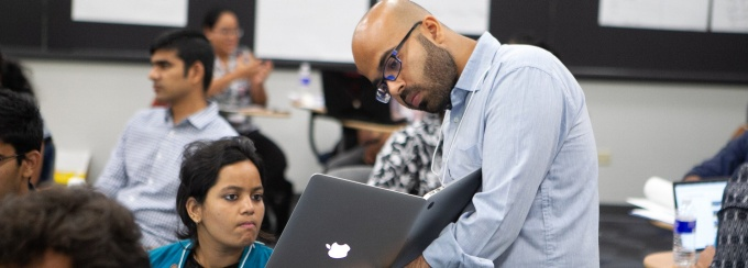 Students sit around a table inside the Blackstone LaunchPad office.