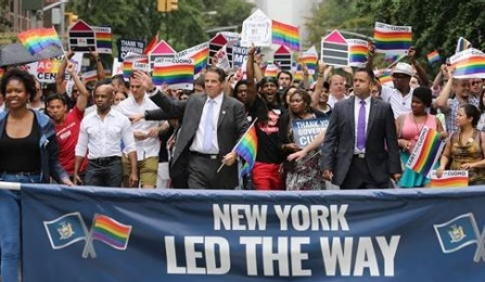 Governor Andrew Cuomo marching in a LGBTQ parade with a banner saying New York Led The Way