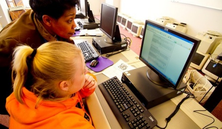 Faculty member helping a student at a computer.