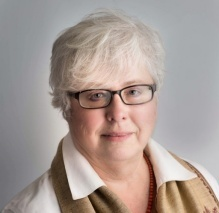 Image of a woman with white hair and dark square glasses wearing a white shirt and a beige vest.