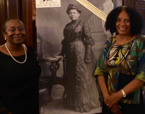 Two women pose in front of a poster depicting Mary Burnett Talbert.