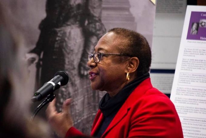 Lillian Williams gives a speech while wearing a red blazer.