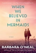 "Book cover of two women on the beach. A pink sunset sky where the title, ""When We Believed in Mermaids"" appears."