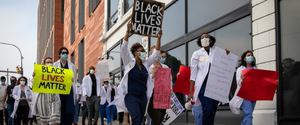 "Faculty, students and others associated with the Jacobs School of Medicine and Biomedical Sciences taking part in a ""White Coats 4 Black Lives"" march on Friday, June 6, 2020 from the Jacobs School to Niagara Square in downtown Buffalo. Some hold up ""Black Lives Matter"" signs, in addition to other signs."