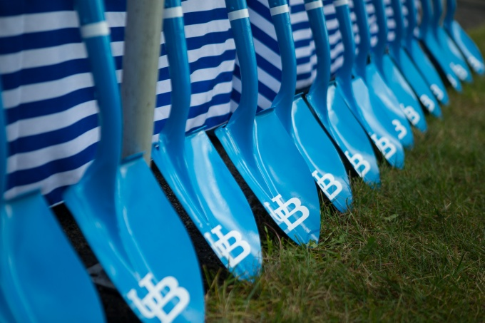 Shovels painted blue with UB logo lined up against a wall.