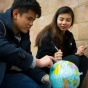 Two students holding a globe.