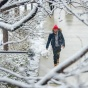 Student walking on snowy campus sidewalk framed by snow covered tree branches.