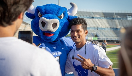 New student taking a picture with Victor E Bull during Welcome Weekend.
