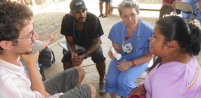 Students discussing how to help a patient in Haiti