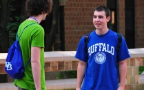 Photo of two male students talking to each other. One wears a bright blue UB t-shirt.