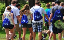 Photo of a group of students wearing bright blue backpacks with a UB logo.