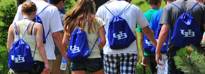 A detail photo of a group of students outdoors, all wearing bright blue UB backpacks.
