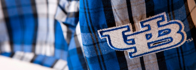A detail photo of the UB logo embroidered on a blue, black and white plaid garment.