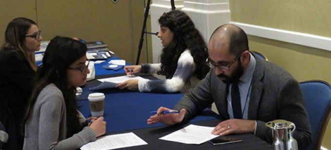 Mentors and mentees discuss job market documents at the annual NeMLA convention.