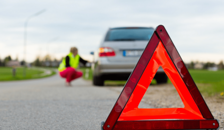 roadside assistance caution triangle in a roadway with car off to side in background.