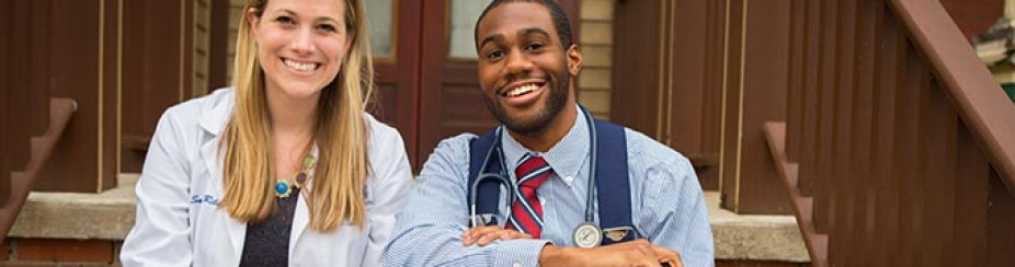 Two medical students smiling and sitting on steps outside/.