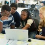 students gathered in front of a laptop, working together on a project.