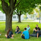 a group of students sitting under a tree on south campus