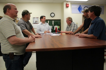 Cutco workers and executives stand around a table.