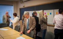 "UB Provost Charles Zukoski joins in an exercise where faculty members write ""wish list"" items for email on post-it notes and categorize them by type of feature on large poster sheets."