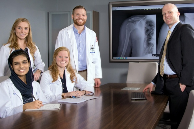 Medical students and professor posing in front of a screen showing an X-Ray of a shoulder.