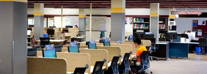 Research stations in a computing site are located near a Library Reference Desk and have a Research name tag attached.