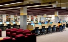 Lockwood 2nd floor library around reference desk with comfortable seating and a row of computers.