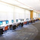 Clement Resdience Hall room 128 computers lined up on tables along windows.