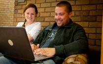 Two students smile and view a laptop screen