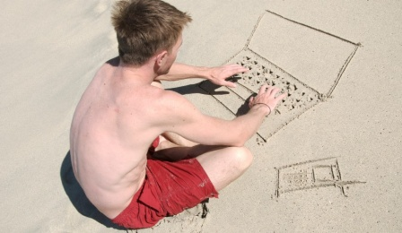 A young man on a beach types into an imaginary laptop that he has drawn in the sand.